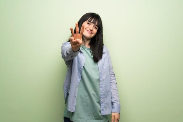 Giovane donna oltre muro verde felice e contando tre con le dita