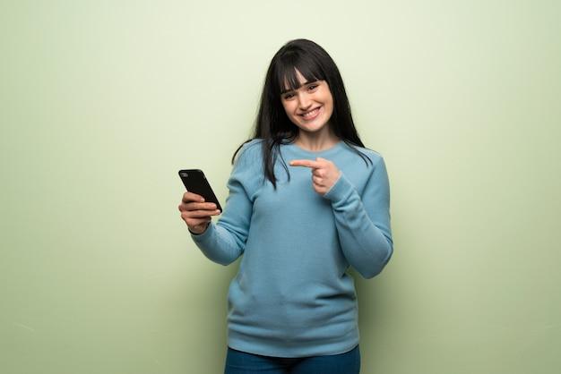 Giovane donna oltre muro verde felice e puntando il cellulare