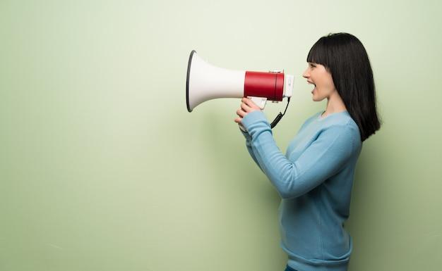 Giovane donna oltre muro verde urlando attraverso un megafono per annunciare qualcosa in posizione laterale