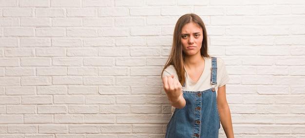 Giovane donna pantaloni a vita bassa che mostra pugno a fronte, espressione arrabbiata