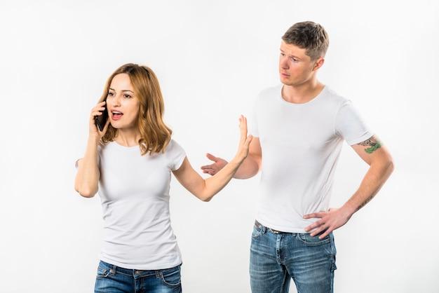 Giovane donna parlando sul cellulare mostrando fermata gesto al suo fidanzato