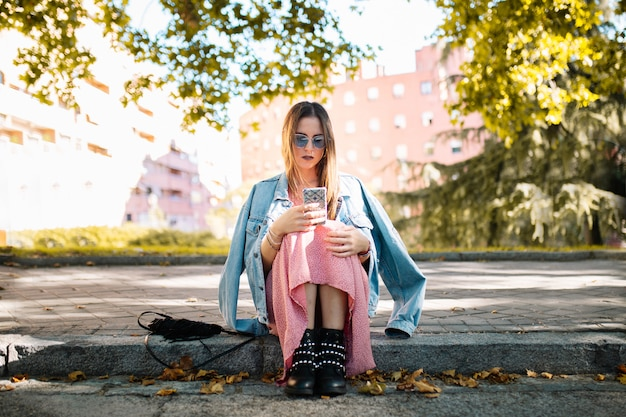 Giovane donna pensierosa con gli occhiali da sole che si siedono sul marciapiede che esamina telefono cellulare che aspetta qualcuno nel parco. emozione umana espressione del viso, sentimento, linguaggio del corpo di reazione. concetto emotivo.