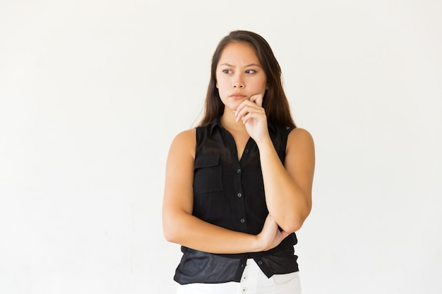 Giovane donna pensierosa con la mano sul mento