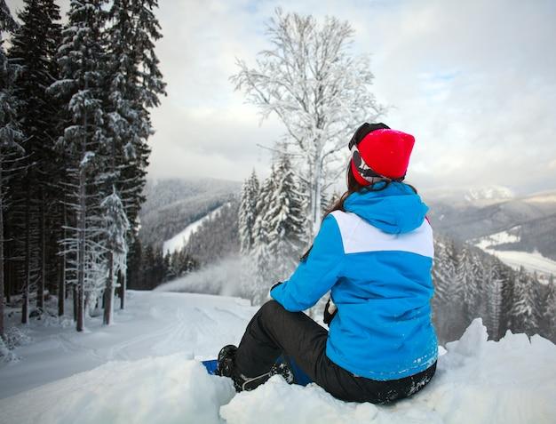 Giovane donna pensierosa in inverno nella foresta nevosa in cima alle montagne