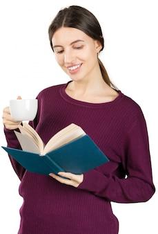 Giovane donna piacevole che legge un libro blu isolato su bianco