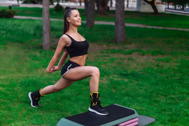 Giovane donna piacevole che si esercita sulla piattaforma a gradini nel parco
