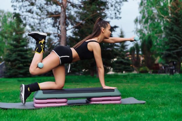 Giovane donna piacevole che si esercita sulla piattaforma di passaggio con manubri nel parco