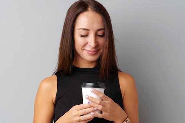 Giovane donna piacevole del brunette che tiene una tazza di caffè