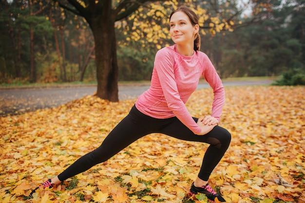 Giovane donna piacevole e allegra che allunga fuori nel parco. lei guarda al lato. la donna si tiene per mano su un ginocchio. è positiva da sola.