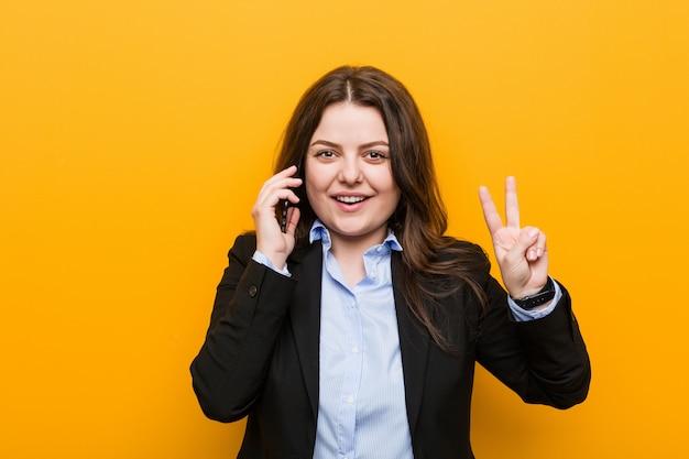 Giovane donna più curvy di affari di dimensione che tiene un telefono che mostra il segno di vittoria e che sorride largamente.
