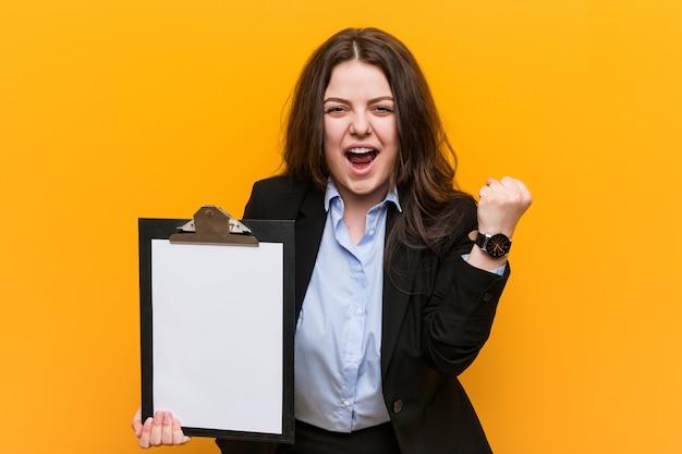Giovane donna più curvy di affari di dimensione che tiene una lavagna per appunti che incoraggia spensierata ed eccitata. concetto di vittoria