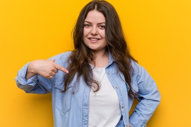 Giovane donna più curvy plus size che punta a mano a una maglietta copyspace, orgoglioso e fiducioso