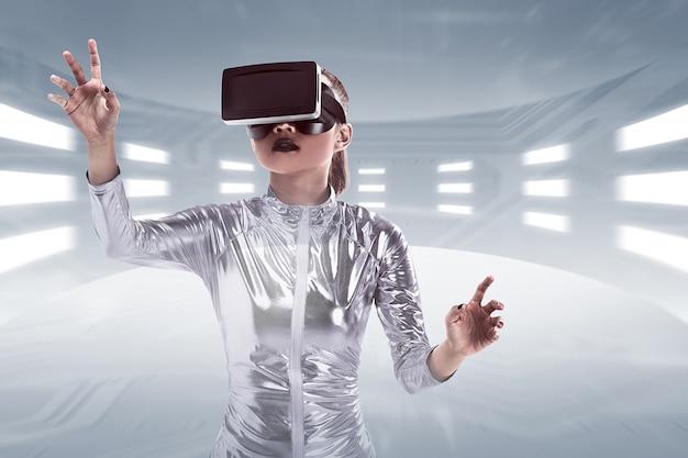 Giovane donna piuttosto asiatica che indossa l'auricolare vr all'interno del mondo virtuale