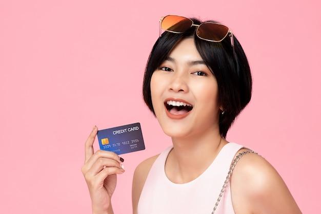 Giovane donna piuttosto asiatica con carta di credito in mano