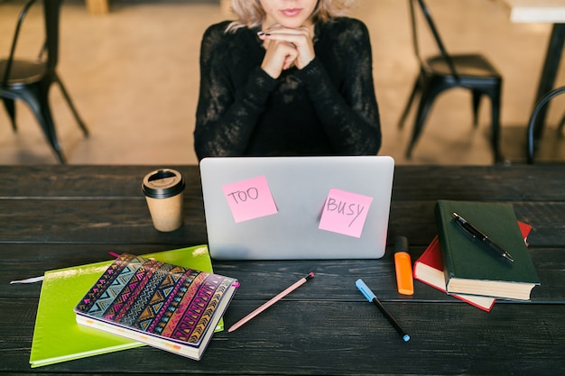 Giovane donna piuttosto impegnata che lavora al computer portatile, adesivi di carta occupati, concentrazione, studente in aula, vista dall'alto sul tavolo con elementi decorativi, non disturbare