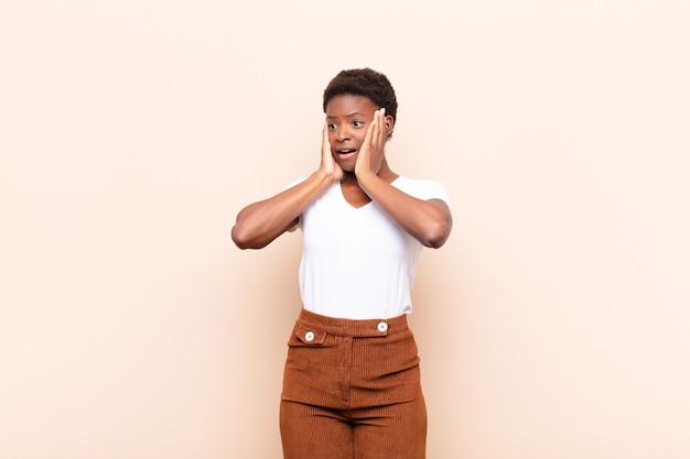 Giovane donna piuttosto nera che si sente felice, eccitata e sorpresa, guardando di lato con entrambe le mani sul viso