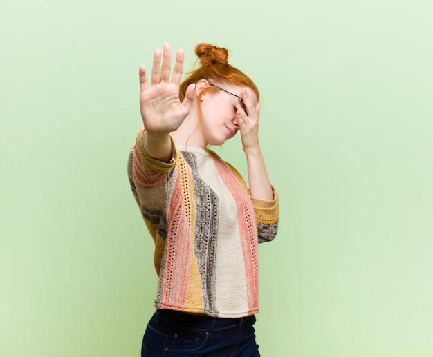 Giovane donna piuttosto rossa testa che copre il viso con la mano e mettendo l'altra mano in alto per fermare la fotocamera, rifiutando foto o immagini sul muro verde