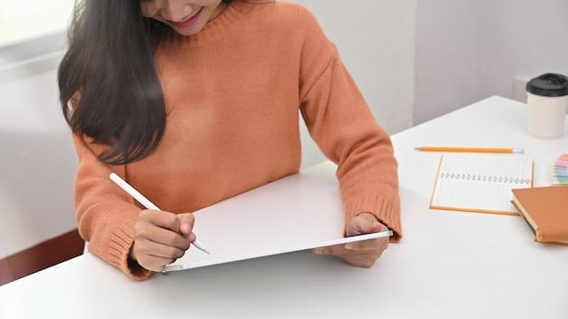 Giovane donna potata del colpo che per mezzo della penna sulla compressa digitale.