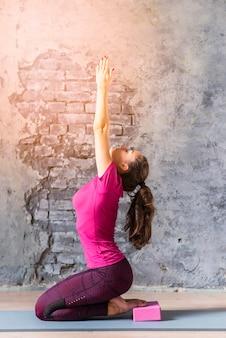 Giovane donna pratica yoga avanzato con blocco rosa
