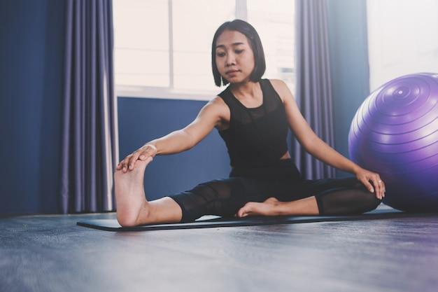 Giovane donna praticare yoga in classe; bella ragazza sentirsi calma e rilassarsi nella lezione di yoga
