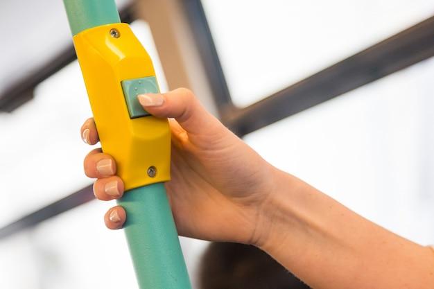 Giovane donna premendo il pulsante di richiesta di arresto sul bus