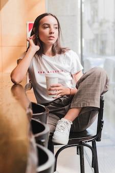 Giovane donna premurosa che si siede sulla sedia in caffè che tiene la tazza di caffè a gettare