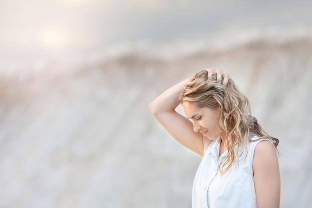 Giovane donna premurosa che sta contro le colline sabbiose chiare.