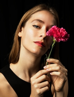 Giovane donna premurosa con garofano rosa