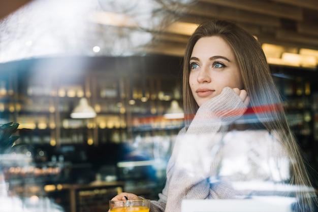 Giovane donna premurosa elegante con la tazza della bevanda in caffè attraverso la finestra