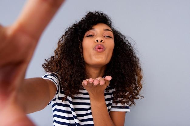 Giovane donna prendendo selfie e soffia un bacio