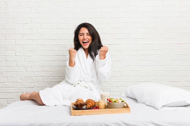Giovane donna prendendo una colazione sul letto tifo spensierato ed eccitato.