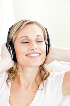 Giovane donna radiosa che ascolta la musica che indossa le cuffie
