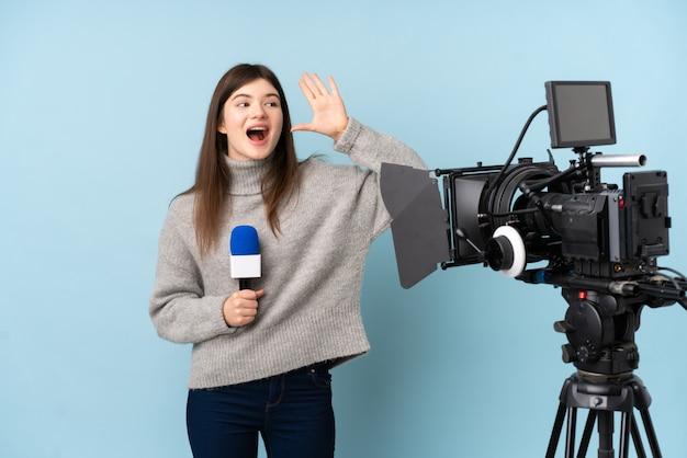 Giovane donna reporter che tiene un microfono e che riferisce le notizie che gridano con la bocca spalancata