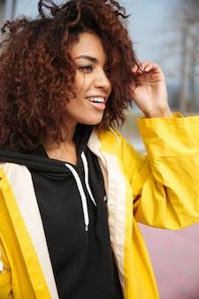 Giovane donna riccia africana felice che porta cappotto giallo