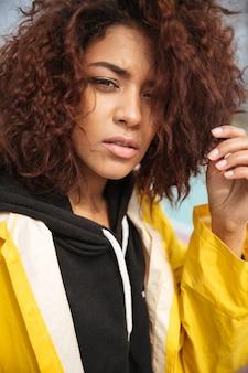 Giovane donna riccia africana seria che porta cappotto giallo