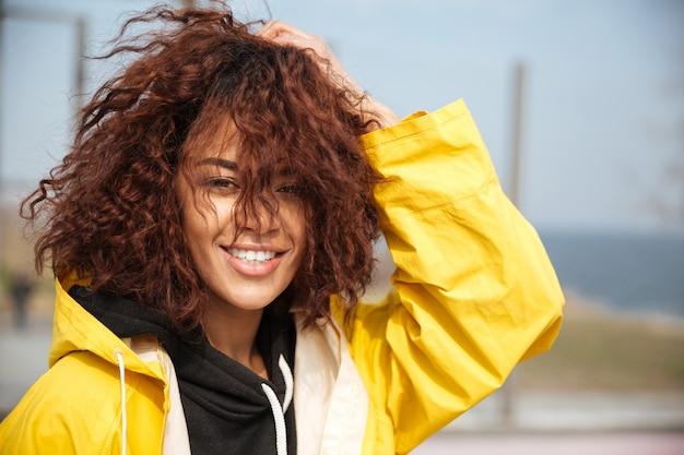 Giovane donna riccia africana sorridente che porta cappotto giallo