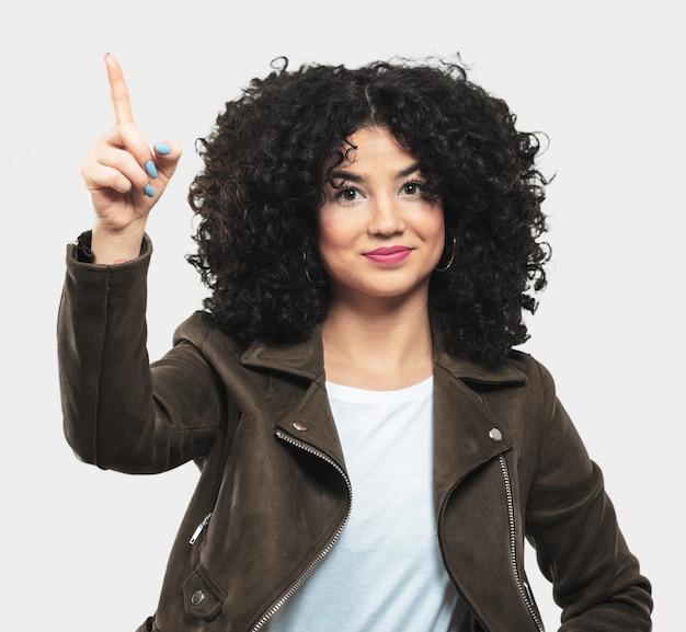 Giovane donna riccia che mostra numero uno