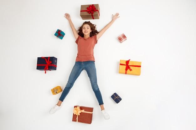 Giovane donna riccia che si trova fra i contenitori di regalo