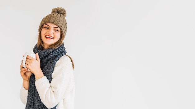 Giovane donna ridendo in cappello e sciarpa con una tazza di bevanda