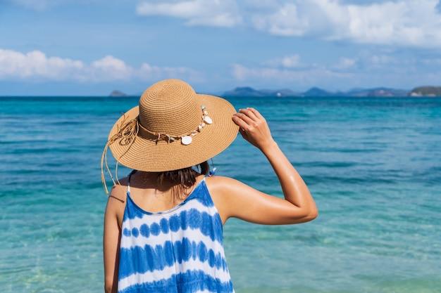 Giovane donna rilassante e godendo in spiaggia tropicale, vacanze estive e concetto di viaggio