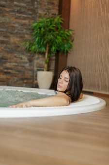 Giovane donna rilassante nella vasca idromassaggio
