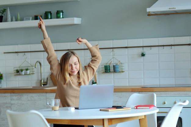 Giovane donna rilassata felice che si siede nella sua cucina con un computer portatile