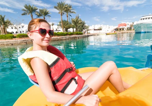 Giovane donna rossa a cavallo catamarano