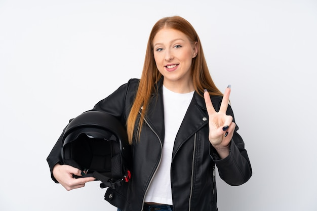 Giovane donna rossa con un casco da motociclista sorridente e mostrando il segno della vittoria