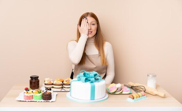 Giovane donna rossa con una grande torta che copre a mano un occhio