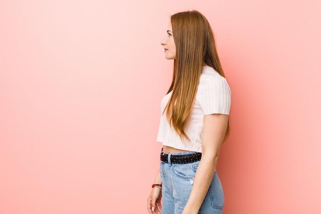 Giovane donna rossa dello zenzero contro una parete rosa che guarda a sinistra, posa laterale.