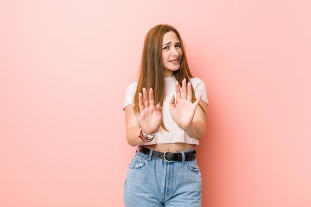 Giovane donna rossa dello zenzero contro una parete rosa che rifiuta qualcuno che mostra un gesto di disgusto.