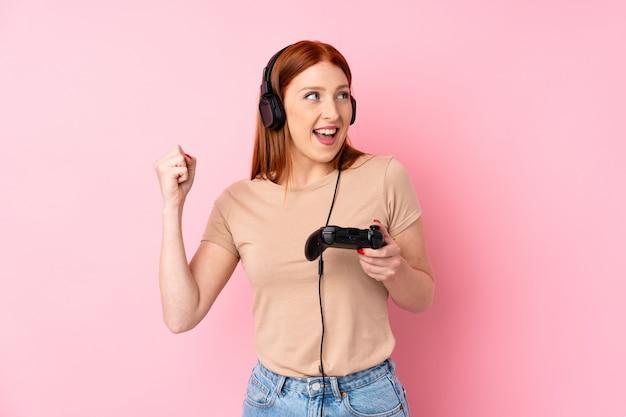 Giovane donna rossa su rosa isolata giocando ai videogiochi
