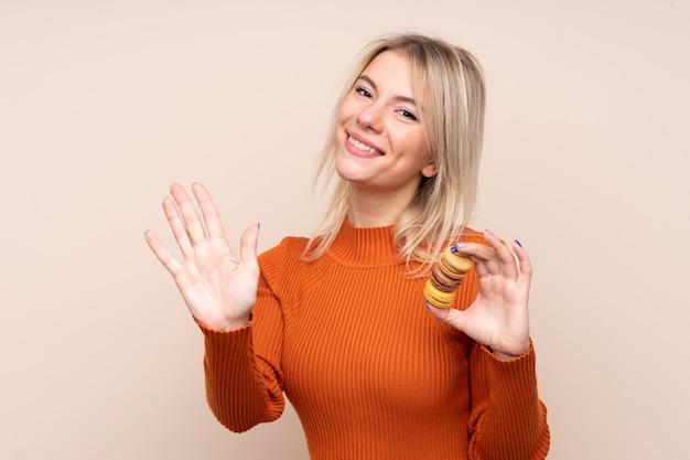 Giovane donna russa bionda sopra la parete isolata che tiene i macarons e il saluto francesi colorati
