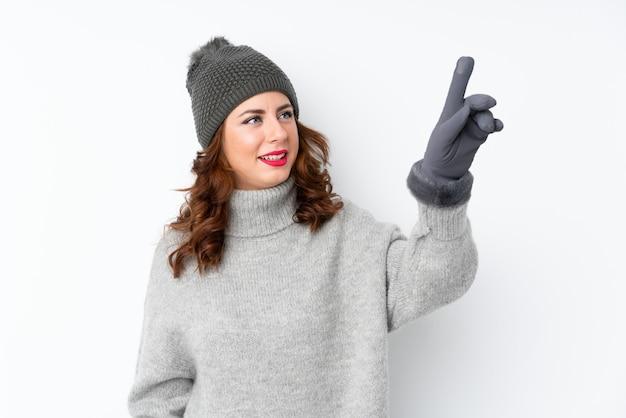 Giovane donna russa con il cappello di inverno sopra bianco isolato toccando sullo schermo trasparente